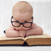funny portrait of cute  baby in glasses lying over an old big book (vintage style); Shutterstock ID 251581639; PO: gennaio
